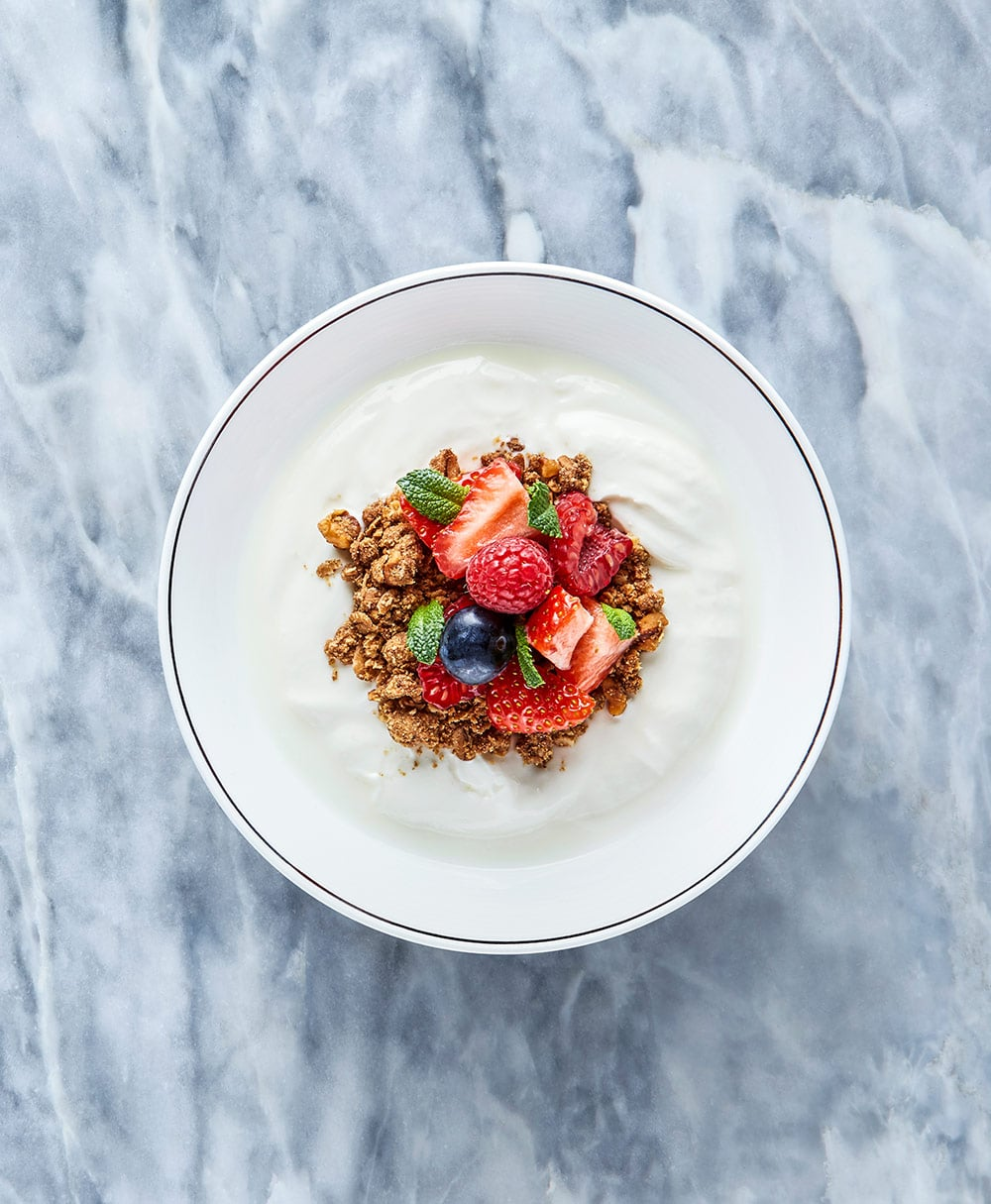 picture of a plate with yoghurt and fruits on marble