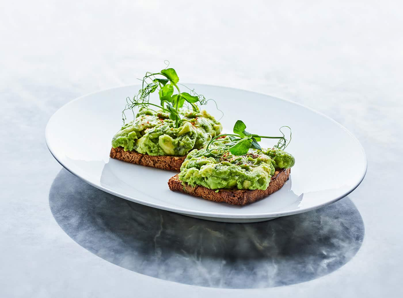 a plate with avocado on a marble tabel